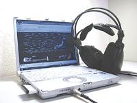 サイマルラジオのウェブサイトと、 阿部さんのヘッドフォン (広島市安佐南区祇園で次田尚弘撮影)