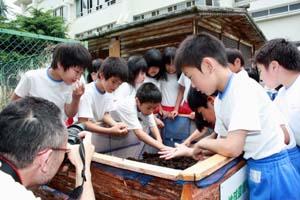 ミミズに触れる小学生らの表情を撮る東京のカメラマン - ミミズのエコ活動、JR山手線で紹介