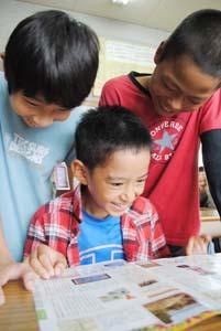 冊子に夢中になる子どもたち(25日、砂山小で) - 白光印刷が児童に文化施設紹介の情報誌配る