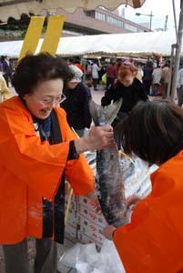 威勢のいい声を上げながらサケを売る販売員たち - 和歌山市駅前で朝市にぎわう