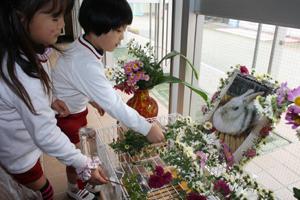 ミミちゃんの遺影にキクの花を供える園児たち