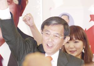 ガンバローコールで拳を突き上げる仁坂さん(午後8時34分、 選挙事務所で)