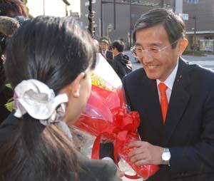 女性職員から花束を受け取り笑顔の仁坂さん - 「また、一緒に仕事だ」仁坂さん2期目スタート