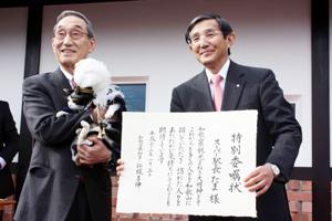 小嶋社長に抱っこされ、 仁坂知事から委嘱状を受けるたま駅長