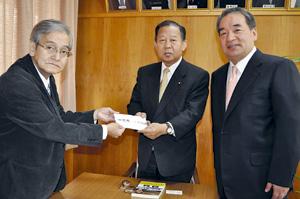 義援金が中田さんから二階本部長に手渡された(11日、自民党県連事務所で)