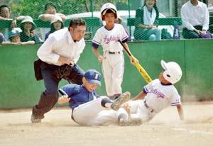 5回裏、暴投で本塁に突っ込む走者を体を張って防いだ今福・射場投手(西支部) - 82チーム激突 和歌山市学童野球支部大会が開幕