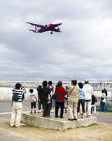 着陸する飛行機に歓声を上げる参加者(関西空港)