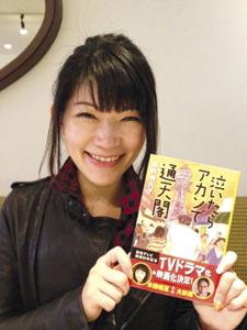 著書を手に 「笑うとビリケンさん似です」 と坂井さん