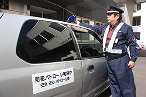 巡回車両に青色回転灯を装着する警備員