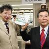 ご当地ナンバーを手にする交付第1号の濵田さん㊧と大橋市長