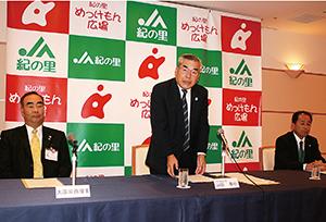 記者会見であいさつする山田組合長(中央)