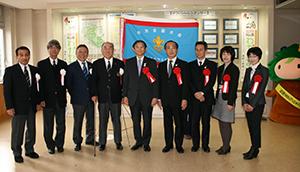 大会旗を囲む関係者(中央の仁坂知事から左に山本理事長、仙石大会実行委員長)