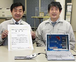 パソコンにつないだ「静電気可視化モニター」と長谷部社長㊧、開発者の中家利幸さん