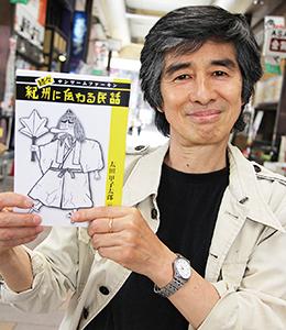 発行した冊子を手に太田さん(ぶらくり丁で)