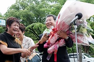 持ちきれないほどの花束を手に笑顔の大橋市長