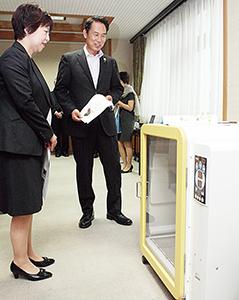 尾花市長㊨に商品(犬用ボックスドライヤー)を説明する担当者