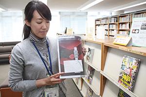 広告掲載部分を指さし応募を呼び掛ける図書館職員