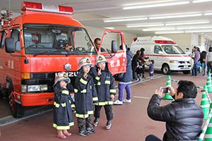 消防車両の前で写真を撮る子ども