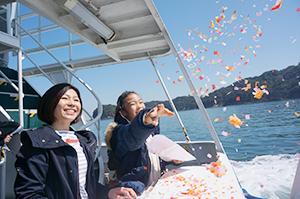 航路の安全を願い海へ清めの紙をまく観光客
