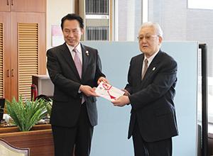 尾花市長㊧から小村代表理事に募金が手渡された