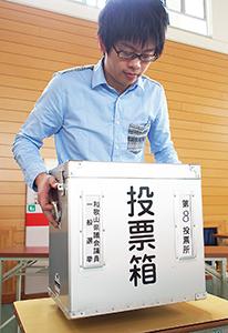 投票箱を設置する職員(11日、大新小で)