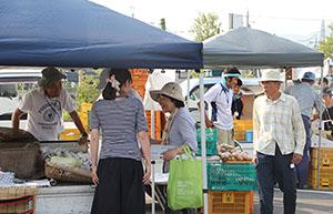 買い物客に野菜を直接販売する農家ら