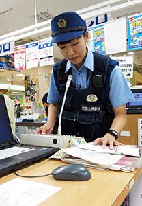 店内放送のマイクで啓発する警察官