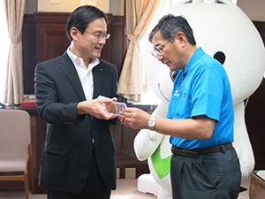 仁坂知事㊨に貨幣セットの説明をする百嶋理事長
