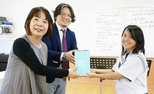 及川さん㊧、中石理事長㊥からコミューンを受け取る生徒会長の松村さん