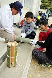 漁師に教わりながらアサリを守る竹筒を作る児童たち