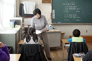 問題用紙を配る教員(和歌山市内の小学校)
