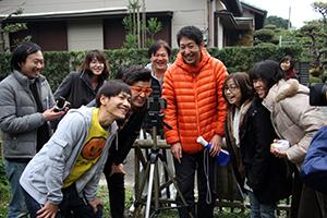 撮影カットを確認する志場さん(中央)と出演者たち