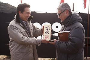 堤監督㊨に日本酒を贈る尾花市長