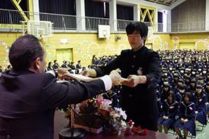 津村校長㊧から卒業証書を受け取る卒業生