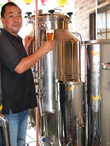 発酵タンクとホップを煮るかまの前で吉田社長