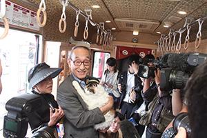 車内で報道陣の取材を受ける小嶋社長とニタマ駅長