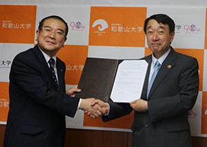 協定書を手に握手する瀧学長㊨と大塚学長