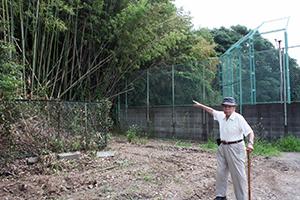 記憶に残るトンネルがあった方向を指さす野村さん(貴志小学校グラウンド西側で)
