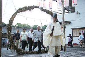 塩﨑宮司を先頭に茅の輪をくぐる参拝者ら