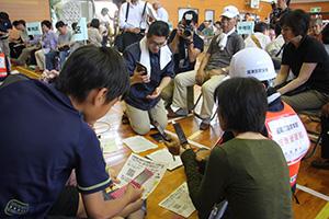 携帯電話から安否情報を入力する参加者ら(塩津小学校)