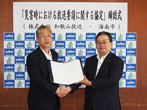 協定書を手に握手する神出市長㊧と中島社長
