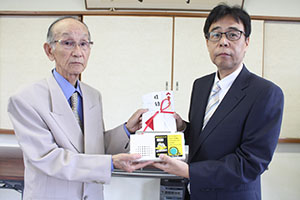 長田社長㊨から野間副会長にラジオが手渡された