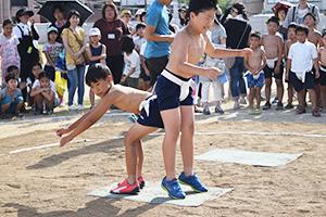 尻相撲で対戦する児童ら