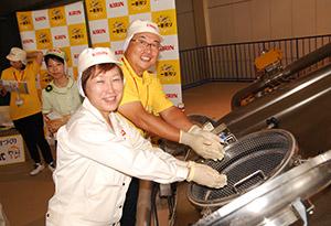 仕込み釜に麦芽を入れる神崎工場長(手前)と伊村支社長