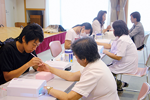 受診者にネイルを施す(奥左から)北野君、宮本さん、尾嵜さん