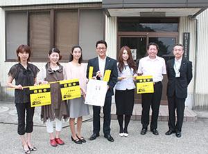黄旗を寄贈した谷口支店長(中央)ら