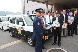 青パトの前で記念撮影した(左から)島署長、宇恵会長、山本さん