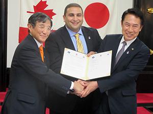 協定書を手に握手するアワディCEO㊥と仁坂知事㊧、尾花市長