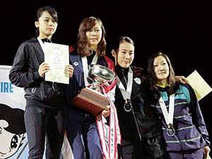 表彰台に立つ東莉央さん㊧と西岡さん(右から2人目)=マザーランド提供=