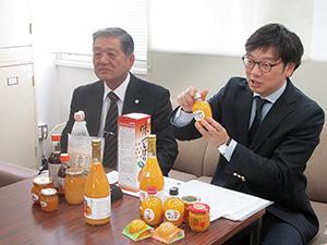 商品を手に機能性表示の取り組みを説明する秋竹専務㊨と秋竹社長